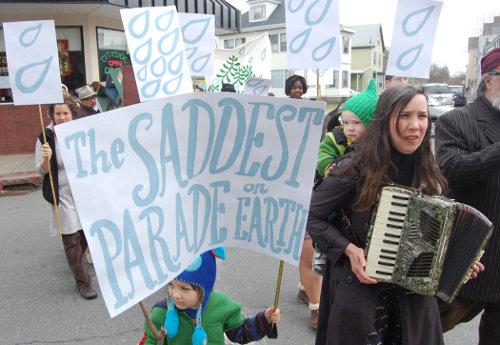 [Image: Jasper Percival Cook holds the parade title as Kari Percival, with son Ulysses on her back, plays accordion. Photo by Greg Cook.]